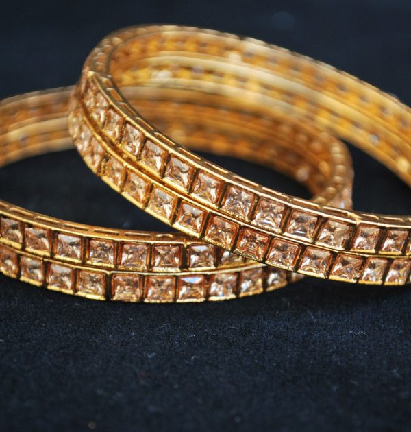 Imitation artificial jewellery gold colour cz copper based bangle.