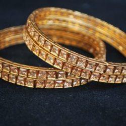 Imitation artificial jewellery gold colour cz copper based bangle.